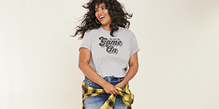Woman wearing a jeans and a collegiate shirt that has the print 'Game On'.