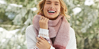 A smiling woman holding in one hand a pink scarf that is wrapped around her neck.